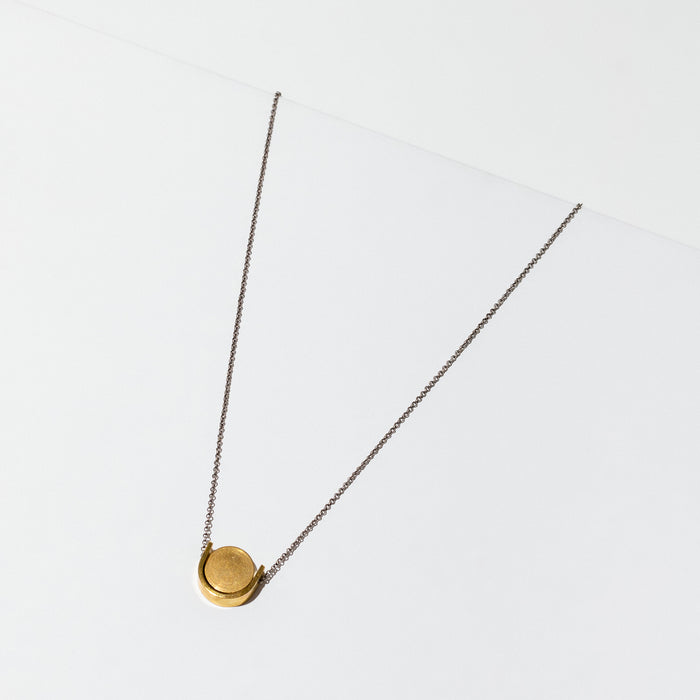Simple brass U shape with a circular disk threaded onto a silver chain. The necklace is 18 inches long with a clasp.
