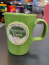 A spring green mug with a round Northfield Yarn logo.