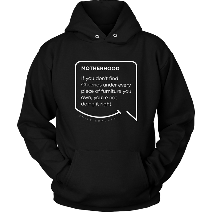 Our funny quotes make the best gifts for Mom! Front view of our soft black hoodie. The modern white quote bubble reads: Motherhood: If you don't find cheerios under every piece of furniture you own, you're not doing it right.