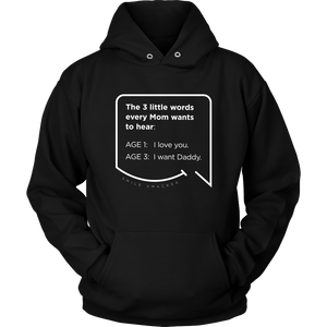Our funny quotes make the best gifts for Mom! Close-up view of our soft black hoodie. The modern white quote bubble reads: The 3 little words every Mom wants to hear. Age 1: I love you. Age 3: I want Daddy.