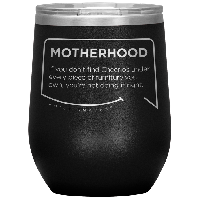 Our funny quotes make the best gifts for Mom! Front view of our chic black wine tumbler. The modern etched quote bubble reads: Motherhood: If you don't find cheerios under every piece of furniture you own, you're not doing it right.