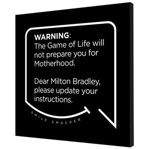 Our funny quotes make the best gifts for Mom! Angled view of our trendy black wall art canvas. The modern white quote bubble reads: Warning: The Game of Life will not prepare you for Motherhood. Dear Milton Bradley, please update your instructions.