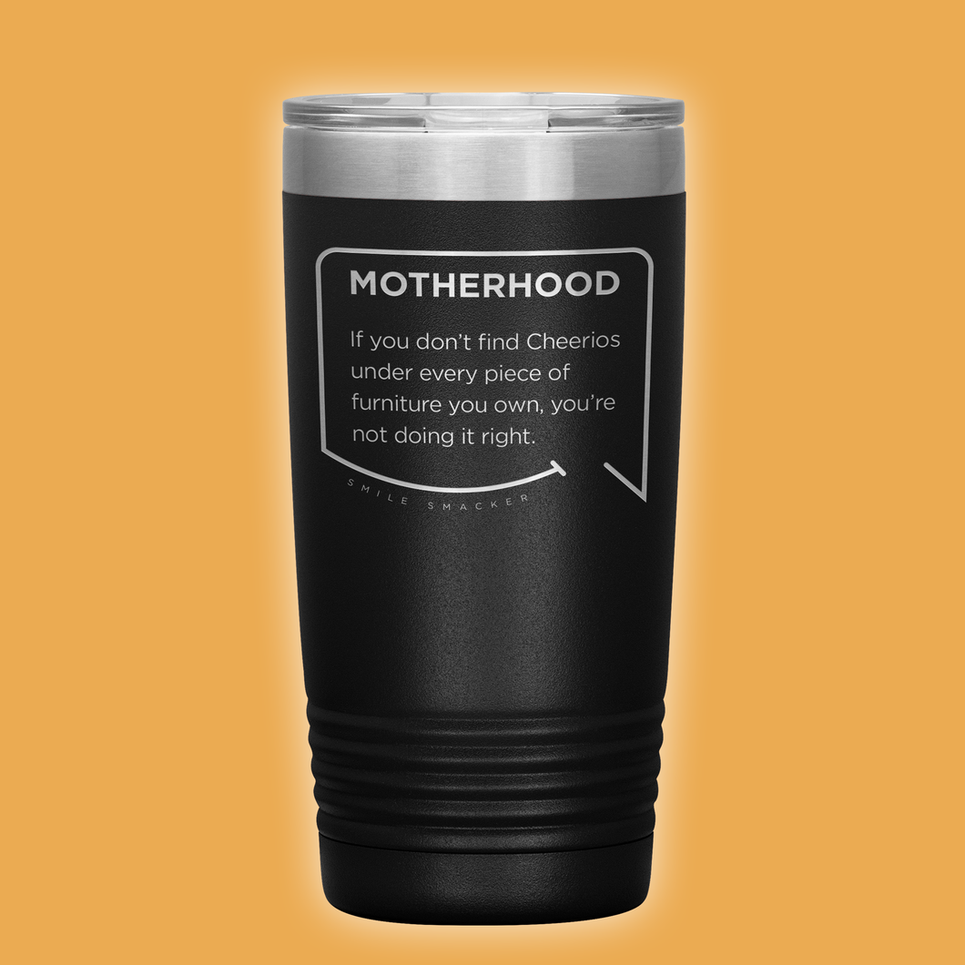 Best mom gifts featuring funny quotes. Front view of our classic 20 oz black travel mug. The modern etched quote bubble reads: Motherhood: If you don't find cheerios under every piece of furniture you own, you're not doing it right.