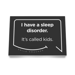 Our funny quotes make the best gifts for Mom! Front view of our trendy black greeting card. The modern white quote bubble reads: I have a sleep disorder. It's called kids.
