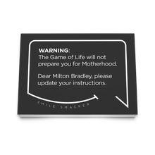 Our funny quotes make the best gifts for Mom! Front view of our trendy black greeting card. The modern white quote bubble reads: Warning: The Game of Life will not prepare you for Motherhood. Dear Milton Bradley, please update your instructions.