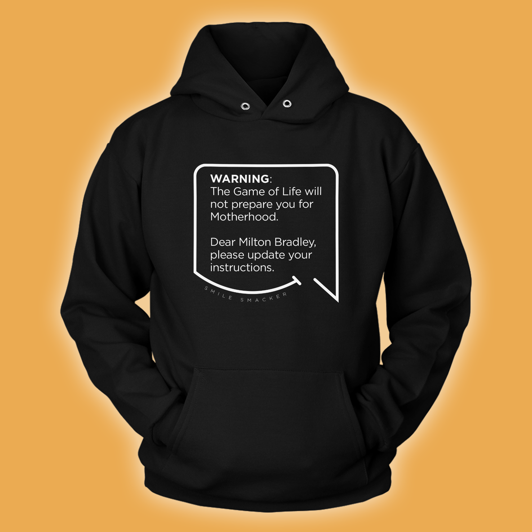 Our funny quotes make the best gifts for Mom! Front view of our soft black hoodie. The modern white quote bubble reads: Warning: The Game of Life will not prepare you for Motherhood. Dear Milton Bradley, please update your instructions.