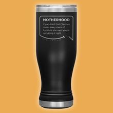 Our funny quotes make the best gifts for Mom! Front view of our popular 20 oz black travel mug. The modern etched quote bubble reads: Motherhood: If you don't find cheerios under every piece of furniture you own, you're not doing it right.