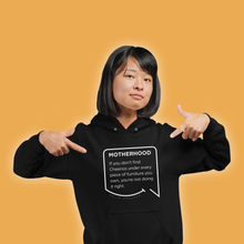 Our funny quotes make the best gifts for Mom! A mom wearing our soft black hoodie is pointing at the modern white quote bubble that reads: Motherhood: If you don't find cheerios under every piece of furniture you own, you're not doing it right.