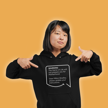 Our funny quotes make the best gifts for Mom! A mom wearing our soft black hoodie is pointing at the modern white quote bubble that reads: Warning: The Game of Life will not prepare you for Motherhood. Dear Milton Bradley, please update your instructions.