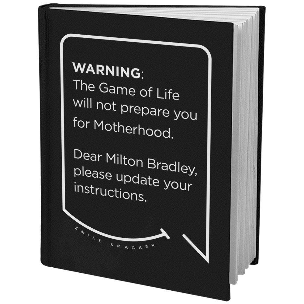 Our funny quotes make the best gifts for Mom! Angled view of our sleek black notebook. The modern white quote bubble reads: Warning: The Game of Life will not prepare you for Motherhood. Dear Milton Bradley, please update your instructions.