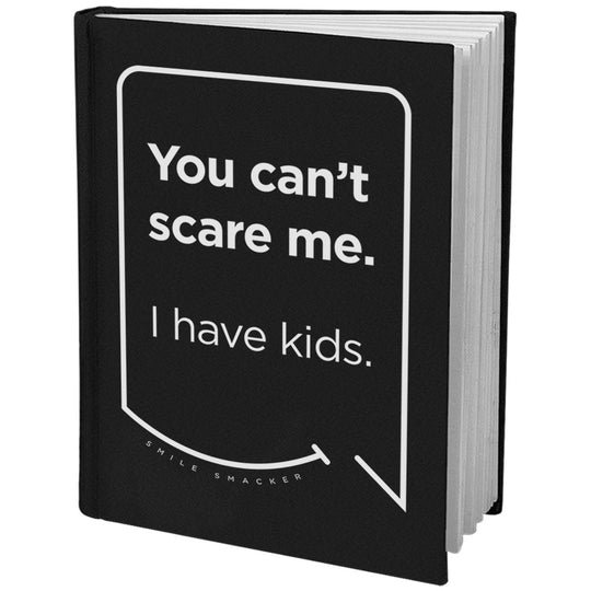 Our funny quotes make the best gifts for Mom! Angled view of our sleek black notebook. The modern white quote bubble reads: You can't scare me. I have kids.