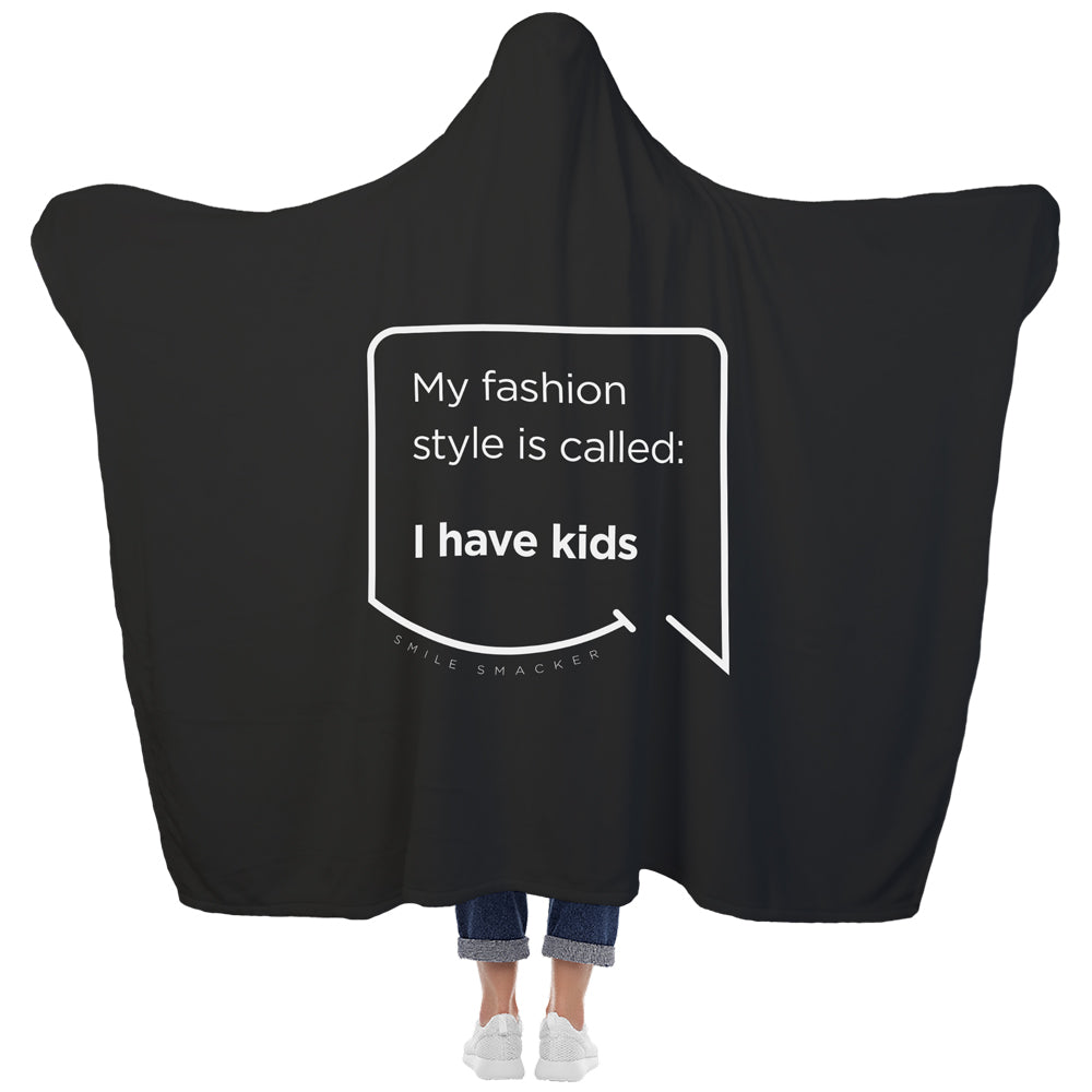 Our funny quotes make the best gifts for Mom! View of our cozy Super-Mom blanket from the back as a Mom holds her arms out to reveal the spacious length and width. The modern white quote bubble reads: My fashion style is called: I have kids.