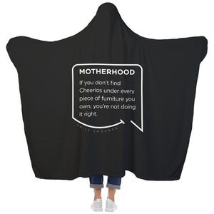 Our funny quotes make the best gifts for Mom! View of our cozy Super-Mom blanket from the back as a Mom holds her arms out to reveal the spacious length and width. The modern white quote bubble reads: Motherhood: If you don't find cheerios under every piece of furniture you own, you're not doing it right.