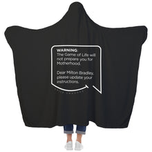 Our funny quotes make the best gifts for Mom! View of our cozy Super-Mom blanket from the back as a Mom holds her arms out to reveal the spacious length and width. The modern white quote bubble reads: Warning: The Game of Life will not prepare you for Motherhood. Dear Milton Bradley, please update your instructions.