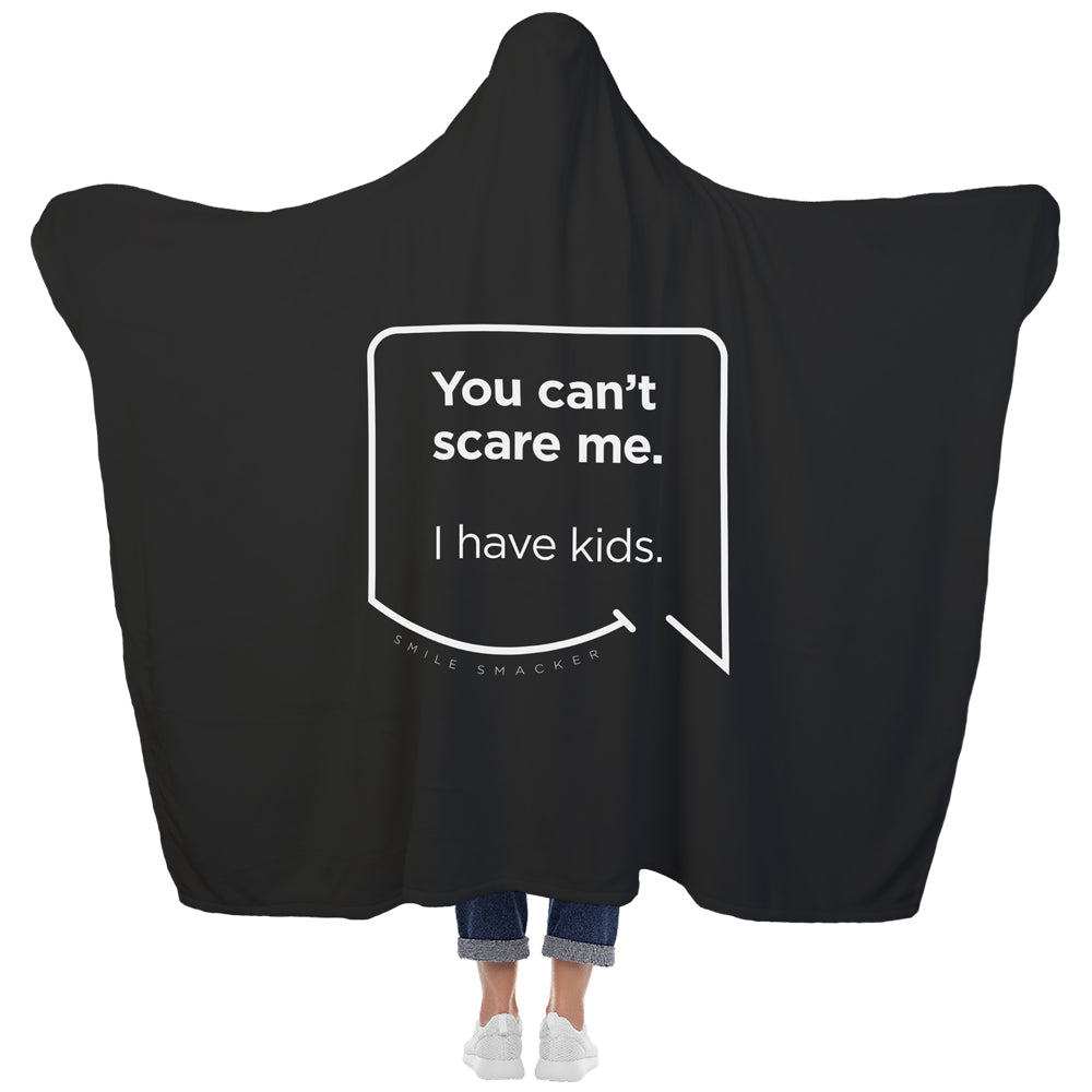 Our funny quotes make the best gifts for Mom! View of our cozy Super-Mom blanket from the back as a Mom holds her arms out to reveal the spacious length and width. The modern white quote bubble reads: You can't scare me. I have kids.