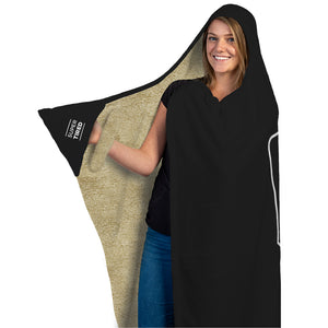"Our funny quotes make the best gifts for Mom! Full length, front view of our cozy Super-Mom blanket with fleece wrist straps, as a Mom holds her right arm out to reveal the words ""Super Tired"" printed on the black mitten pocket."
