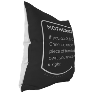Our funny quotes make the best gifts for Mom! This side view of our chic throw pillow shows the contrast between the white back and black front, with a modern white quote bubble that reads: Motherhood: If you don't find cheerios under every piece of furniture you own, you're not doing it right.