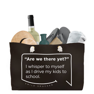 Our funny quotes make the best gifts for Mom! Front view of our large, black, double-sided weekender bag filled with travel items. The modern white quote bubble reads: Are we there yet? I whisper to myself as I drive my kids to school.