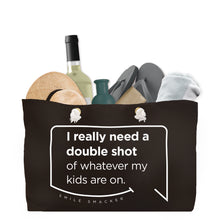 Our funny quotes make the best gifts for Mom! Front view of our large, black, double-sided weekender bag filled with travel items. The modern white quote bubble reads: I really need a double shot of whatever my kids are on.