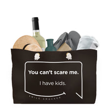 Our funny quotes make the best gifts for Mom! Front view of our large, black, double-sided weekender bag filled with travel items. The modern white quote bubble reads: You can't scare me. I have kids.