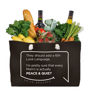 Our funny quotes make the best gifts for Mom! Front view of our large, black, double-sided weekender bag filled with groceries. The modern white quote bubble reads: They should add a 6th Love Language. I'm pretty sure that every Mom's is actually Peace and Quiet.