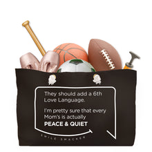 Our funny quotes make the best gifts for Mom! Front view of our large, black, double-sided weekender bag filled with dance and sports equipment. The modern white quote bubble reads: They should add a 6th Love Language. I'm pretty sure that every Mom's is actually Peace and Quiet.