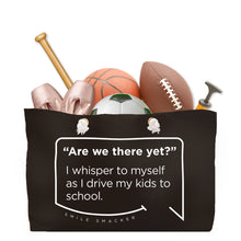 Our funny quotes make the best gifts for Mom! Front view of our large, black, double-sided weekender bag filled with dance and sports equipment. The modern white quote bubble reads: Are we there yet? I whisper to myself as I drive my kids to school.