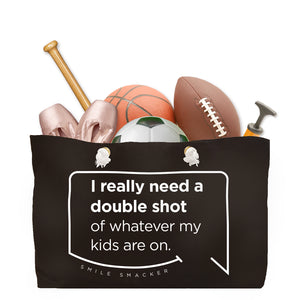 Our funny quotes make the best gifts for Mom! Front view of our large, black, double-sided weekender bag filled with dance and sports equipment. The modern white quote bubble reads: I really need a double shot of whatever my kids are on.