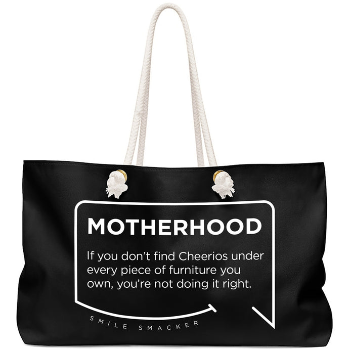 Our funny quotes make the best gifts for Mom! Front view of our large, black, double-sided weekender bag. The modern white quote bubble reads: Motherhood: If you don't find cheerios under every piece of furniture you own, you're not doing it right.
