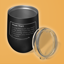 Our funny quotes make the best gifts for Mom! Overhead view of our chic black wine tumbler. The modern etched quote bubble reads: Mom Trait: Crying because you need a day away from the kids, then crying when you get it because you miss them so much.