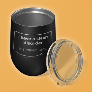 Our funny quotes make the best gifts for Mom! Overhead view of our chic black wine tumbler. The modern etched quote bubble reads: I have a sleep disorder. It's called kids.