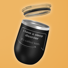 Our funny quotes make the best gifts for Mom! Tilted view of our chic black wine tumbler with a clear lid. The modern etched quote bubble reads: I have a sleep disorder. It's called kids.