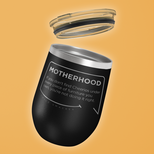 Our funny quotes make the best gifts for Mom! Tilted view of our chic black wine tumbler with a clear lid. The modern etched quote bubble reads: Motherhood: If you don't find cheerios under every piece of furniture you own, you're not doing it right.