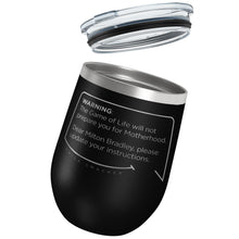Our funny quotes make the best gifts for Mom! Tilted view of our chic black wine tumbler with a clear lid. The modern etched quote bubble reads: Warning: The Game of Life will not prepare you for Motherhood. Dear Milton Bradley, please update your instructions.