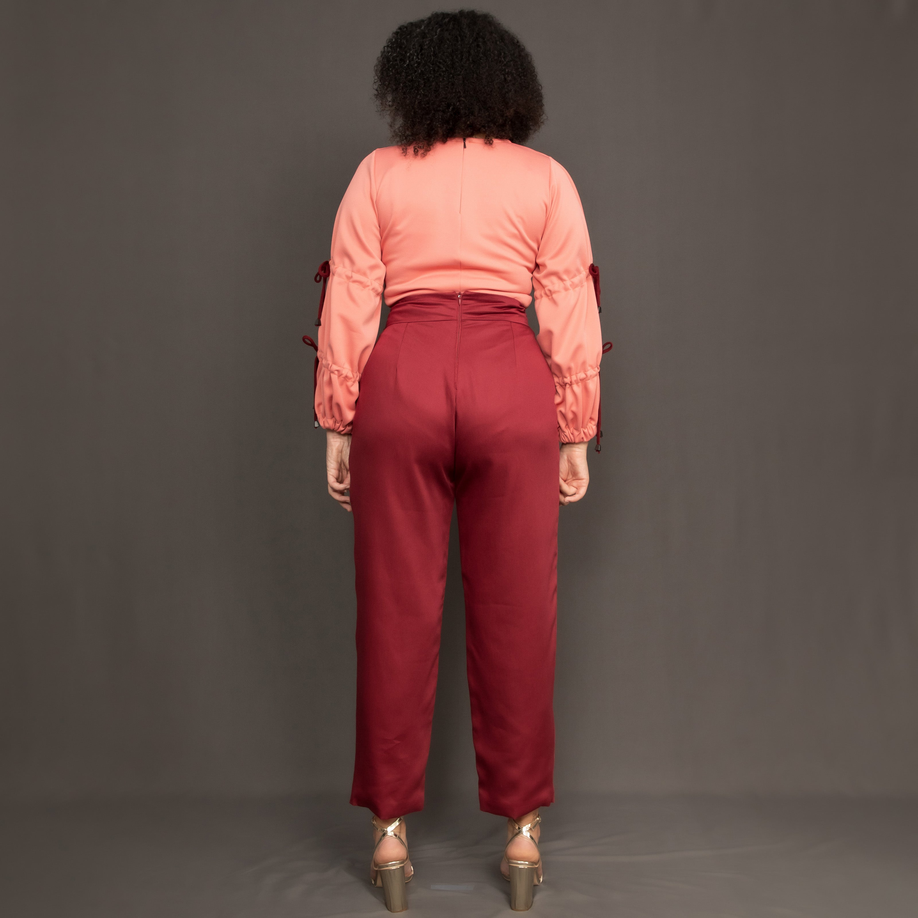 Model wearing high waist burgundy trousers and salmon pink long sleeve top by Kim Dave