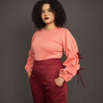 Salmon pink scuba top with drawstring detail on sleeves paired with burgundy trouser