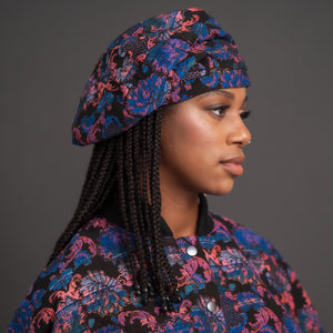 Black model wearing multi colour beret made with jacquard fabric.