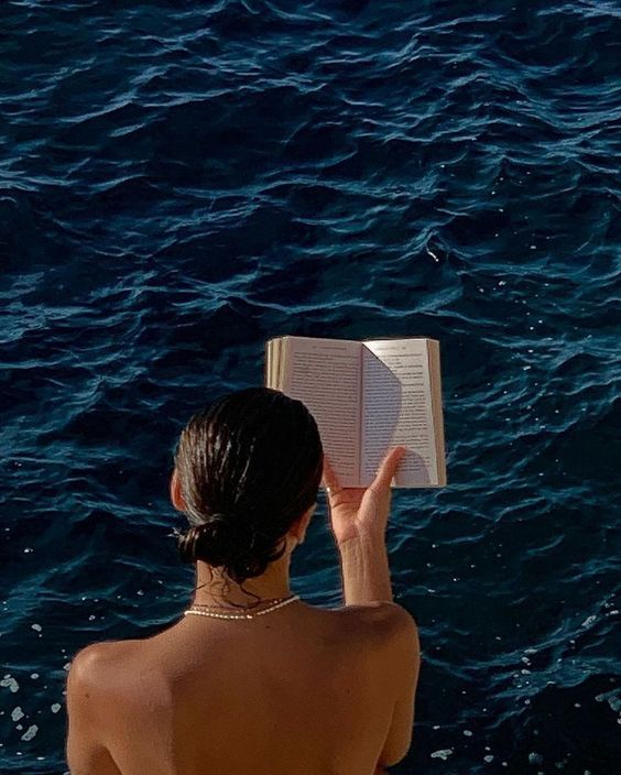 A young female model reading a novel while on holidays