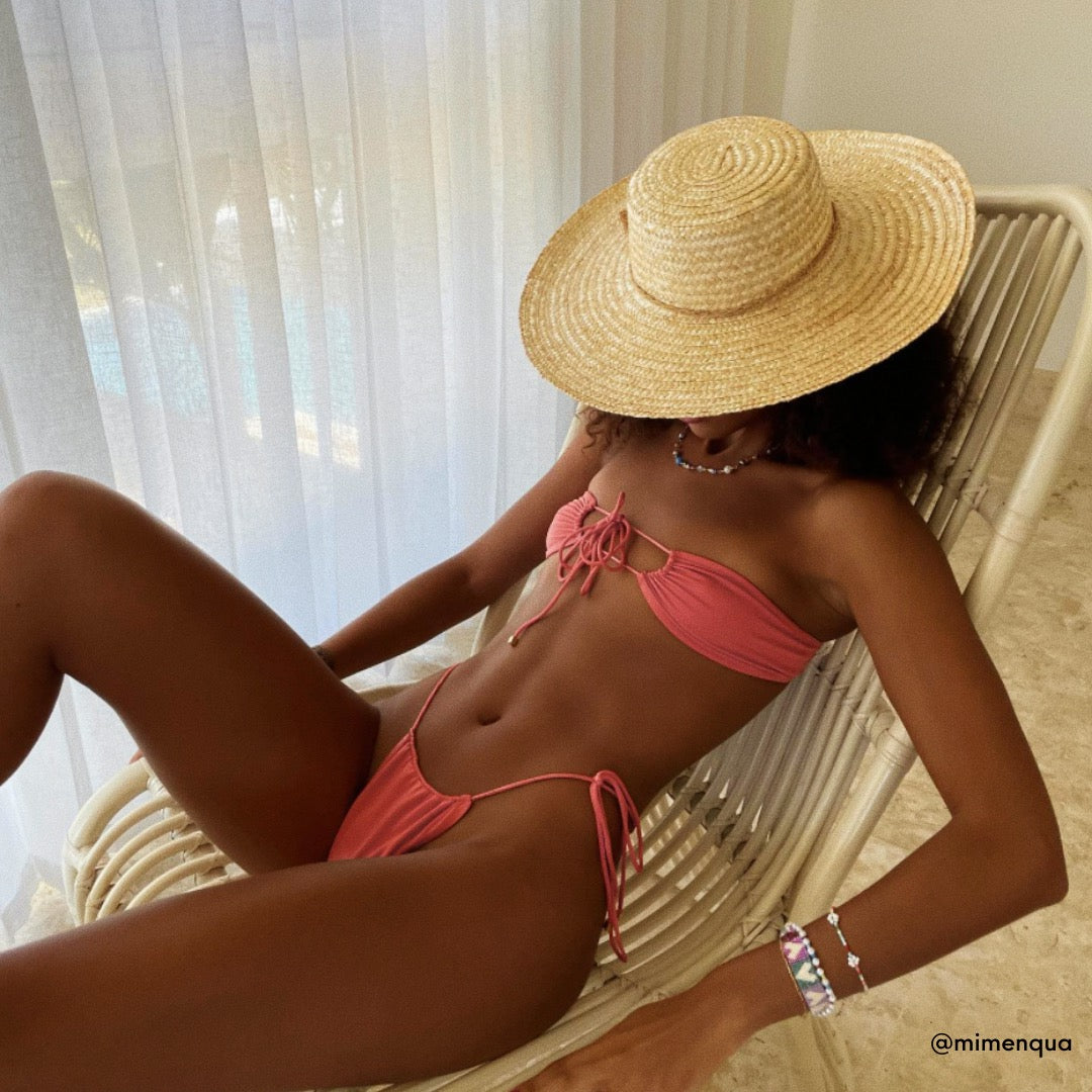 Model Mirian Quadros poses for a photo wearing a straw sun hat wearing Sommer Swim's Coral Xena halter neck bikini top with accompanying bikini bottoms.