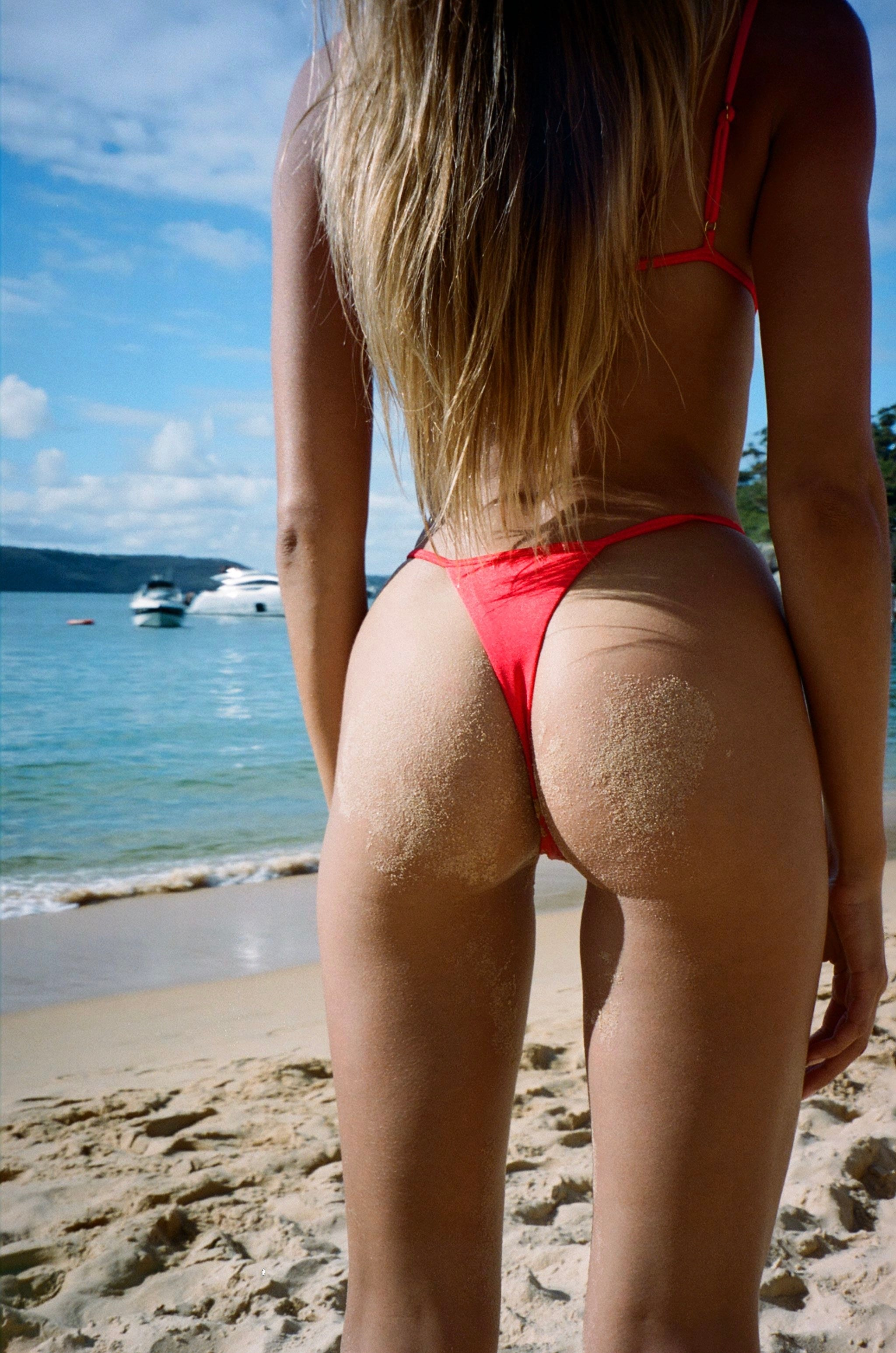 Model facing the beach with back to the camera wearing bright red sommer swim thong bikini bottom
