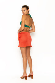 Sommer Swim model facing backwards and wearing Salinas mini wrap skirt in Campari