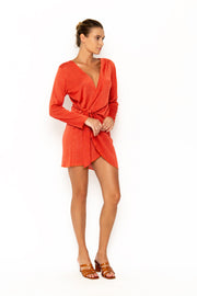 Sommer Swim model facing sideways to the left and wearing Madeira Wrap dress in Campari