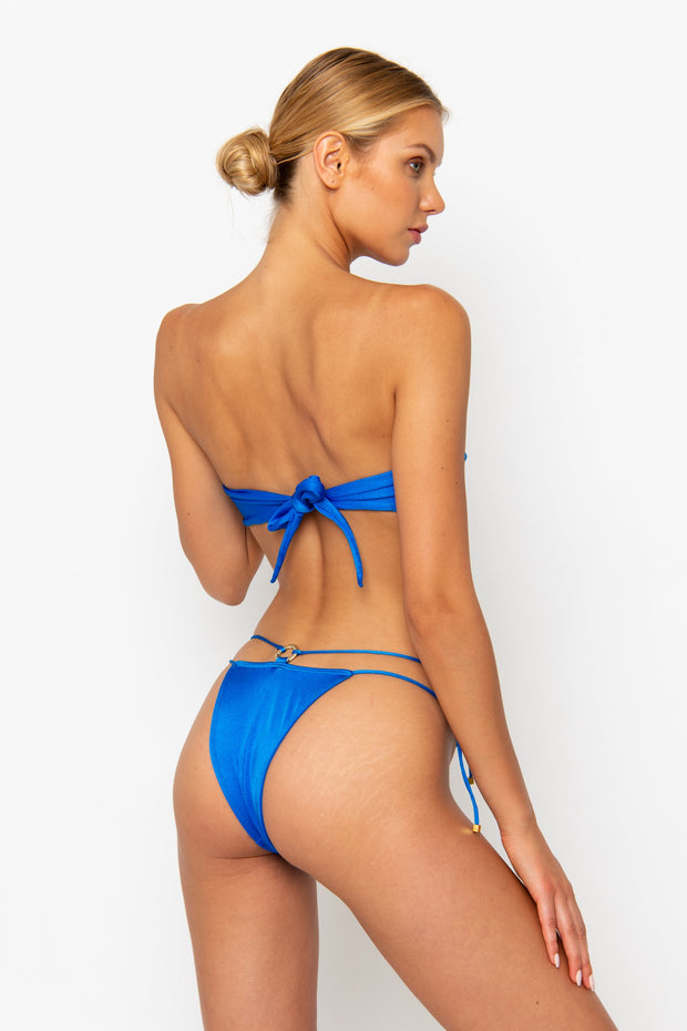 Sommer Swim model is facing backwards and wearing a Cece Bandeau bikini top in Sirius
