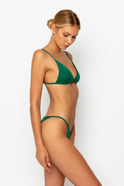 Sommer Swim model facing sideways to the left and is wearing a Eden cheeky bikini bottom in Emerald