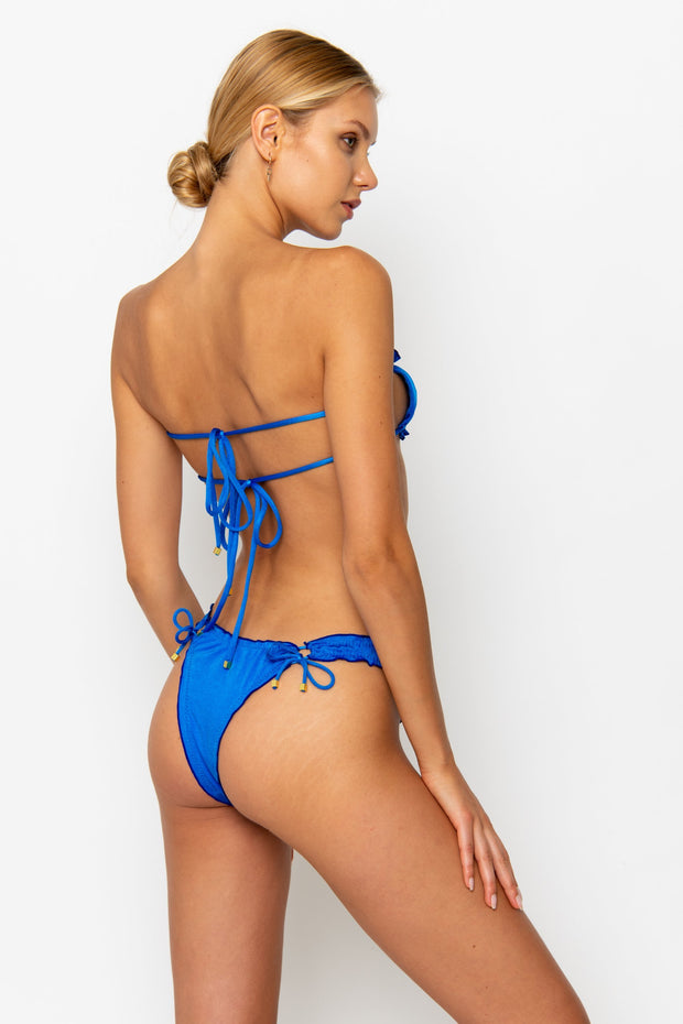 Sommer Swim model facing backwards wearing a Esmee adjustable halter style bikini top in Sirius