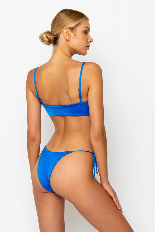 Sommer Swim model facing backwards and wearing Gia tie front bikini top in Sirius