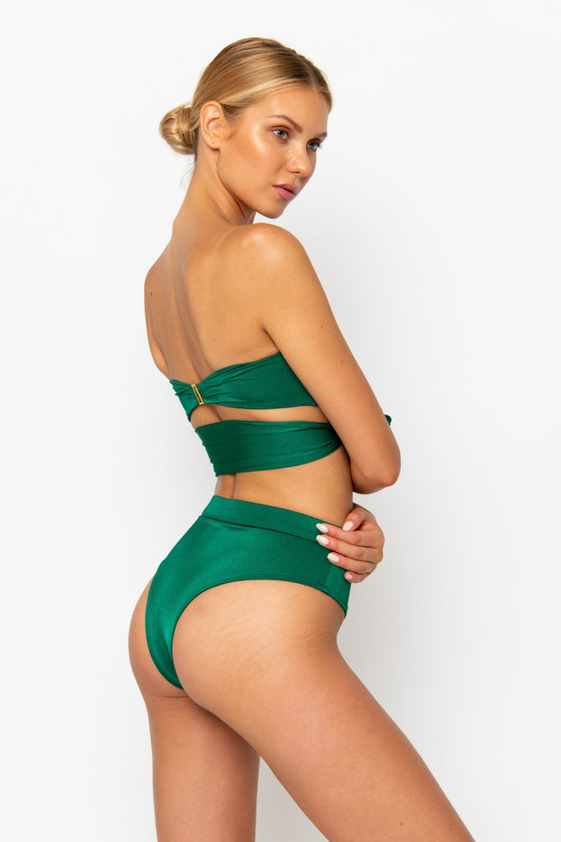 Sommer Swim Model facing backwards and wearing a Harlow bandeau bikini top in Emerald