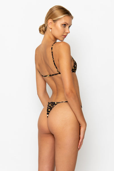 Sommer Swim model facing backwards and wearing a thong bikini bottom in Leopard Luxe