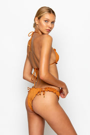 Sommer Swim model facing sideways to the left and wearing a Josephine brazilian bikini bottom in Papagayo