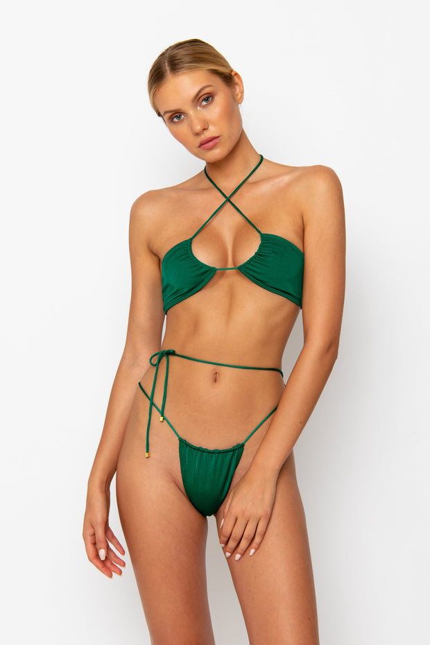 Sommer Swim model facing forwards and wearing a Naomi tie side bikini bottom in Emerald